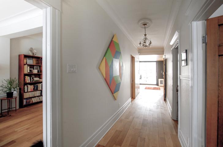 La restauration des moulures et des portes intérieures a permis la préservation du  cachet de l'axe de circulation principal de la maison et de suggérer une continuité avec la cour arrière.