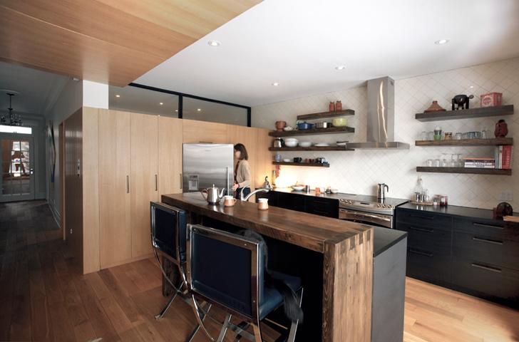 Un bloc d'armoires de cuisine avec finition en chêne blanc crée un lien contemporain avec le corridor de la maison d'origine.