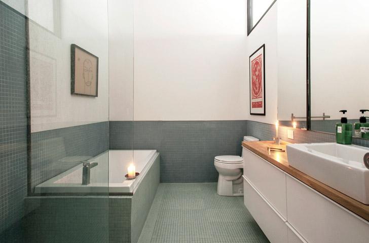 La céramique murale, le bandeau de fenêtre et les grands miroirs donnent de l'ampleur à la nouvelle salle de bain.