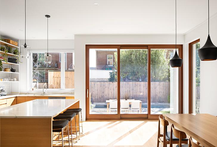 La cuisine/salle-à-manger bénéficie d'une importante entrée de lumière naturelle permise par une ouverture généreuse sur la cour.