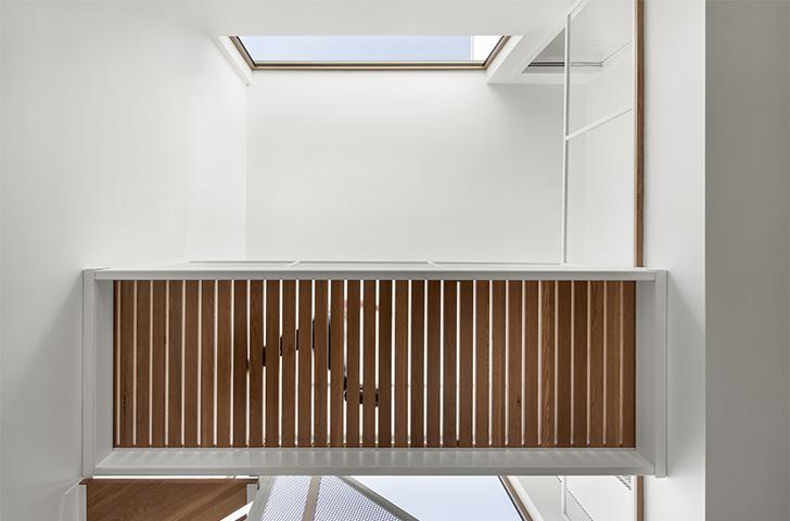 Un plancher de lattes de bois ajourées, ainsi qu'un garde-corps de métal déployée assurent une transparence visuelle qui amplifie la relation entre les niveaux.
